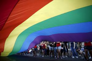 Gay rights activists raise a huge rainbow flag during a Gay Pride parade in Athens, June 13, 2015. REUTERS/Kostas Tsironis